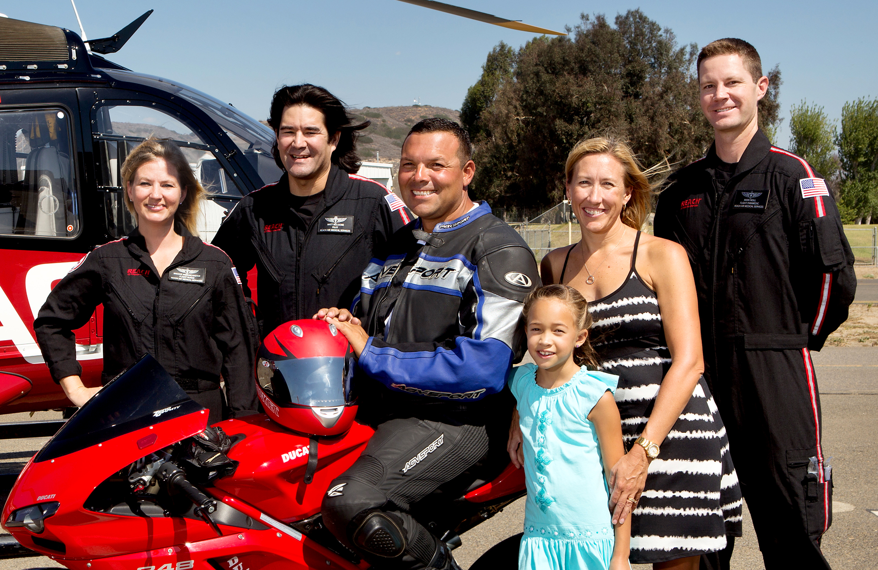 Brian Cortez, on motorcycle, is joined by (left to right) REACH Flight Nurse Brooke Inscore-Raster, Pilot Matt McLuckie, wife Amy, daughter Madison. and REACH Flight Paramedic Mark Neill.